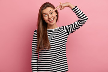 Happy pleasant looking young woman shoots in temple, has broad tender smile, has fun alone, pretends making suicide gesture, tilts head, wears striped casual jumper, isolated over pink background.