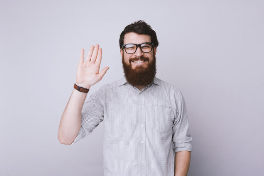 Hi, nice to meet you. Happy man with beard looking at cmera and greeting