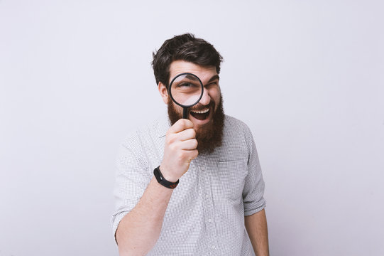 Portrait of handsome bearded man with magnifying glass, funny elder amazement investigation