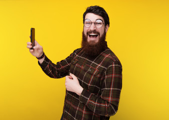 Happy smiling bearded guy in round glasses taking sellfie while looking at camera