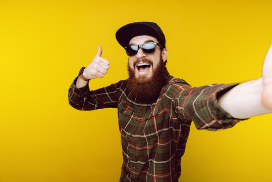 Like ! Bearded guy taking selfie in black hat and sunglasses and gesturing thumb up, good, like symbol