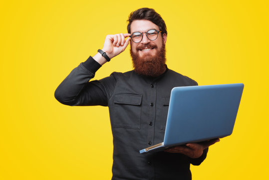 Portrait of happy smart bearded guy, holding a laptopand touchig his glasses