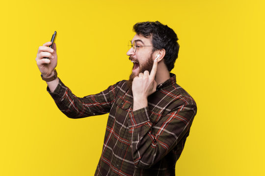 Portrait of  excited bearded guy using a smartphone and listening music on airpods