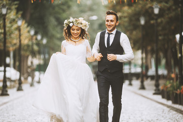 A loving couple of newlyweds walks in the city. Husband and wife happy smiling on a walk