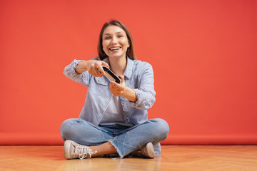 Excited casual young woman playing video games having fun on red background