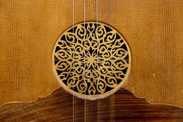 Close up at the circle of the sound hole at the soundboard of Greek traditional wooden music instrument with strings of lute decorated with flower