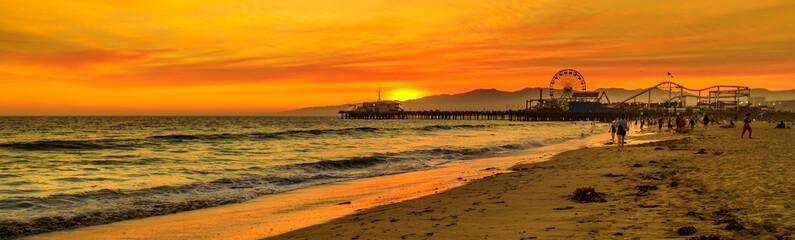 Scenic landscape of iconic Santa Monica Pier at orange sunset sky from the beach on Paficif Ocean. Santa Monica Historic Landmark, California, USA. Wide banner panorama. Fototapete