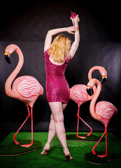 cute girl in fuchsia sequins dress resting and dancing with three big flamingos on black background