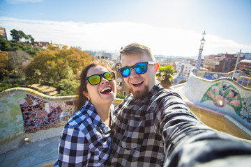Travel couple happy making selfie portrait with smartphone in Park Guell, Barcelona, Spain.