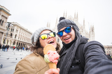 Travel in winter and Italy concept - Happy young couple take selfie photo with ice-cream in front of Milan Duomo Cathedral.