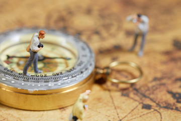 Travelling concepts. Group of traveler miniature mini figures with camera standing and walking on old world map
