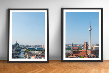 two framed pictures of Berlin skyline on wooden floor white wall background  -