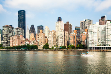 View of midtown Manhattan skyline and sailboat that is cruising on East River during sunny summer day