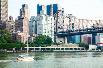 View of midtown Manhattan skyline and sailboat that is cruising on East River with Queensboro bridge in background during sunny summer day