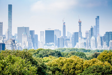 Futuristic look of Manhattan skyline viewed from Central Park in New York City during sunny summer day