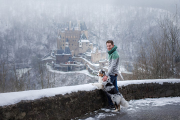 a young man and a dog at the castle. Walk with your pet. australian shepherd on nature in winter