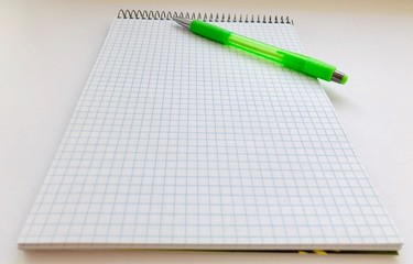 Checkered Notepad and a pencil on a white background. Things for study and work. Top view of a pad and pencil