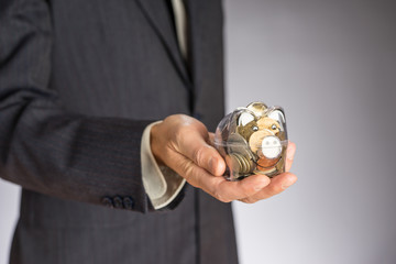 Business man with gray jacket putting euro coin  into the  piggi bank. European finance currency. Guy holding money box