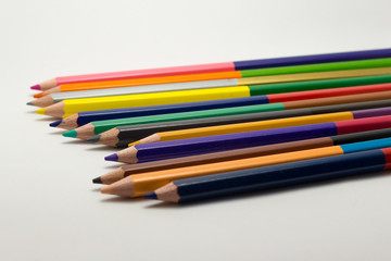 Double sided mulitcolored pencils in a row on white background.
