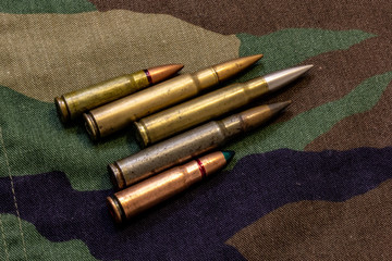 Five rifle bullets on military camouflage coat at background