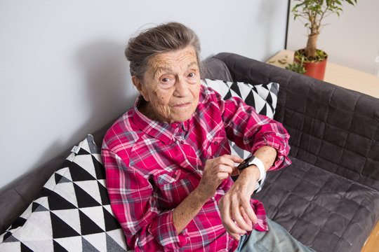 A very old senior Caucasian grandmother with gray hair and deep wrinkles sits at home on the couch in jeans and a red plaid shirt and uses a smart watch on her wrist. Pensioner and technology