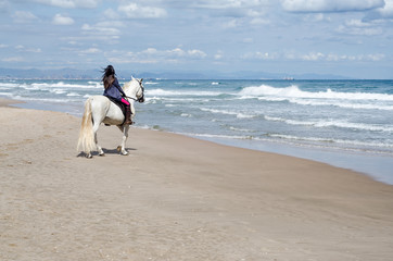 young woman riding along the beach with his white horse, sees the city in the background
