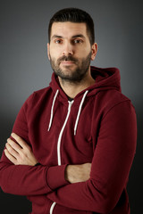 Portrait of handsome bearded man in a red hoodie against the black background