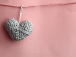 Handmade knitted heart on pink background. Happy Valentines Day. 14 February greeting card