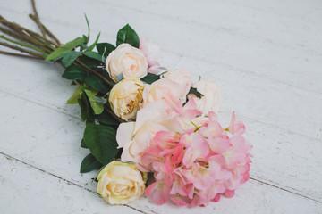 Tender light roses on white wooden background
