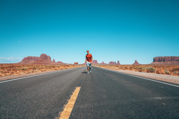 Young man walking down the Monument Valley road.