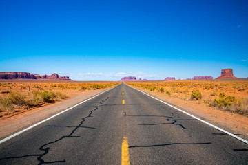 Photo sur Plexiglas Route 66 Endless infinite road that goes through the Monument Valley National park with amazing rock formations.