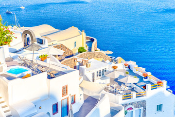 Famous European Destinations. Breathtaking View of Classic White Roofed Houses and Pastel-Blue Colors of Oia Village on Santorini Island in Greece With Boats in Background.