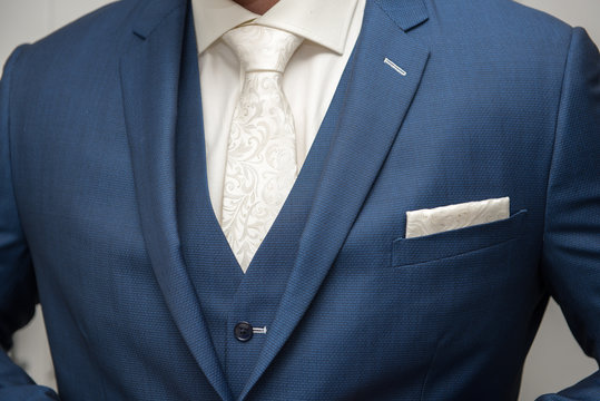 Grooms morning preperation closeup, blue suit