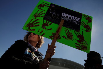 A woman holds a sign during a march by members of Border Network for Human Rights to protest against U.S. President Donald Trump's proposed wall, in El Paso