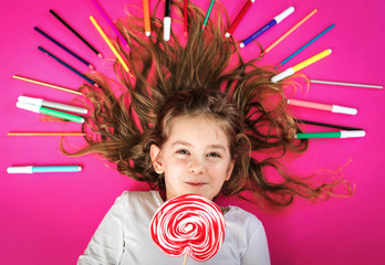 little girl with color pencils and lollipop