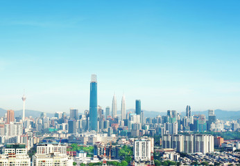 Cityscape of Kuala lumpur city skyline on blue sky with sunlight in Malaysia at daytime.