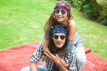 Young attractive smiling man and woman with long hair and in sunglasses are sitting on the carpet with pillows. Hippie and gypsy style.
