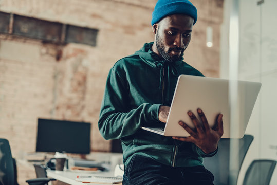 Waist up of calm man sitting with laptop in his hands