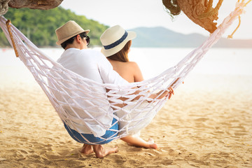 Young happy couple relaxing on the beach on a hammock