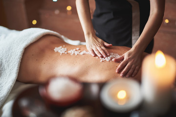 Therapist apply mineral salt on lady back