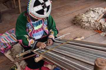 Pisac, Cusco, Peru - Oct 20, 2018: Quechua woman demonstrating traditional weaving techniques at a market in the Sacred Valley.