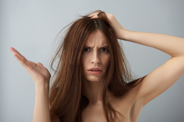Displeased and confused girl demonstrating her damaged hair