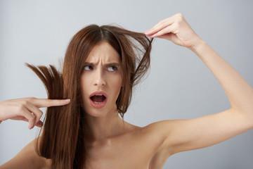 Shocked girl with naked shoulders demonstrating her damaged hair