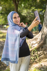 Happy young Asian woman take selfie with her smartphone at blurred park background.