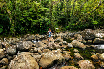 Young woman crossing stream on a trail to Middle Tavoro Waterfalls in Bouma National Heritage Park, Taveuni Island, Fiji