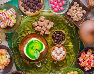 Tea break with a delicious honey cake decorated in the form of a green apple and a variety of multi-colored small candies. Copper and clay plates in a composition with jugs. Arab concept