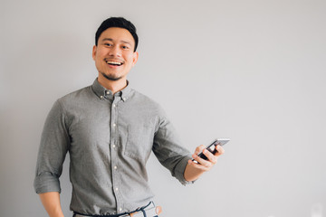 Happy and wow face of Asian man use smartphone on isolated gray background.