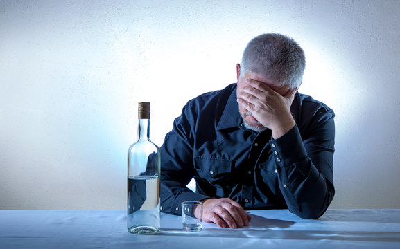 a man is desperately sitting at a table with a bottle of alcohol