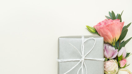 Womens day present. Silver gift box and fresh flowers. Copy space on ivory background. Flat lay.