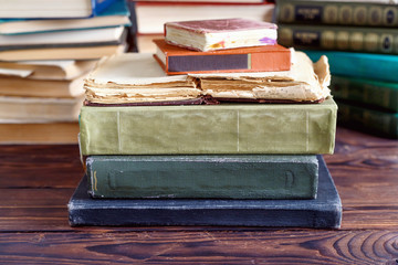 Stack of old vintage books on wooden shelf in  university library